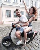 Jeunes couples gais montant un scooter et ayant l'amusement Photos libres de droits
