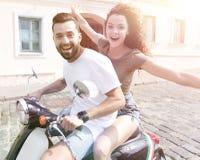 Jeunes couples gais montant un scooter et ayant l'amusement Photo stock