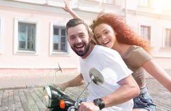 Jeunes couples gais montant un scooter et ayant l'amusement Image libre de droits