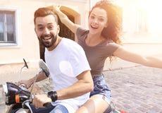 Jeunes couples gais montant un scooter et ayant l'amusement Image stock