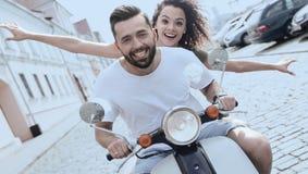 Jeunes couples gais montant un scooter et ayant l'amusement Photo libre de droits