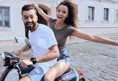 Jeunes couples gais montant un scooter et ayant l'amusement Photographie stock