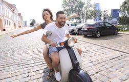 Jeunes couples gais montant un scooter et ayant l'amusement Photos stock