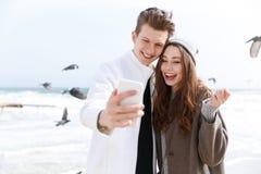 Jeunes couples gais prenant le selfie avec le smartphone en automne Photographie stock