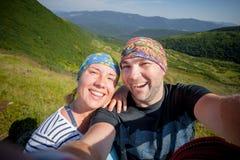 Jeunes couples gais prenant le selfie dehors Image stock