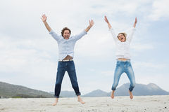 Jeunes couples gais sautant à la plage Photographie stock libre de droits