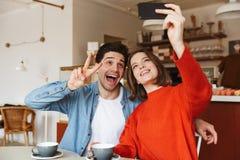 Jeunes couples gais se reposant à une table de café Image stock