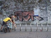 Jeunes couples garant leurs bicyclettes en ville à un support de bicyclette devant un mur de graffiti photos libres de droits