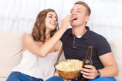 Jeunes couples gentils se reposant sur le divan Photos stock