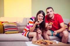 Jeunes couples géniaux mangeant de la pizza sur un divan Image libre de droits