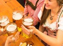 Jeunes couples grillant dans la tente de bière d'Oktoberfest Photographie stock