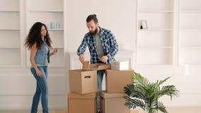 Jeunes couples heureux à la maison en mouvement décorant la pièce clips vidéos