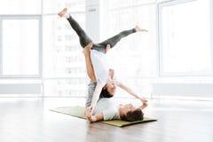Jeunes couples heureux équilibrant et faisant le yog d'acro Image libre de droits