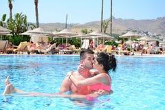 Jeunes couples heureux étreignant et embrassant dans la piscine Photos libres de droits