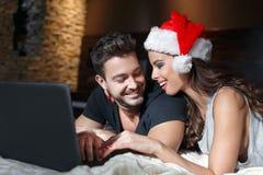 Jeunes couples heureux achetant le cadeau en ligne de Noël Photos libres de droits