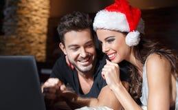 Jeunes couples heureux achetant le cadeau en ligne de Noël par l'ordinateur portable Photo libre de droits