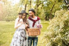 Jeunes couples heureux allant avoir le picninc en parc photos libres de droits