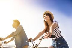 Jeunes couples heureux allant pour le tour de bicyclette Photos stock