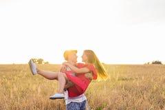 Jeunes couples heureux appréciant dans le domaine de blé, saison d'été Lumière de coucher du soleil, lumière de fusée, l'espace d Photos libres de droits