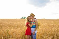 Jeunes couples heureux appréciant dans le domaine de blé, saison d'été Lumière de coucher du soleil, lumière de fusée, l'espace d Photographie stock