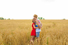 Jeunes couples heureux appréciant dans le domaine de blé, saison d'été Lumière de coucher du soleil, lumière de fusée, l'espace d Photos stock