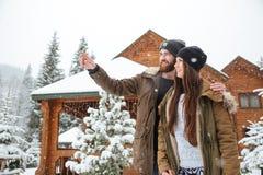 Jeunes couples heureux appréciant la vue des montagnes d'hiver Photographie stock libre de droits
