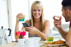 Jeunes couples heureux appréciant le petit déjeuner dans la cuisine Images stock