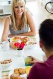 Jeunes couples heureux appréciant le petit déjeuner dans la cuisine Photo stock