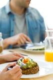 Jeunes couples heureux appréciant le petit déjeuner dans la cuisine Image stock