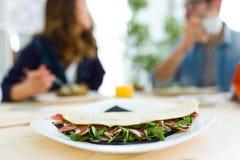 Jeunes couples heureux appréciant le petit déjeuner dans la cuisine Photographie stock