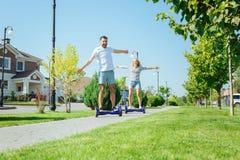 Jeunes couples heureux appréciant le tour de hoverboard Images stock
