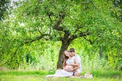 Jeunes couples heureux attendant le bébé, femme enceinte avec le ventre émouvant de mari Photographie stock libre de droits