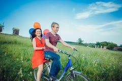 Jeunes couples heureux ayant l'amusement allant dehors pour un tour avec la bicyclette dans la campagne Images stock