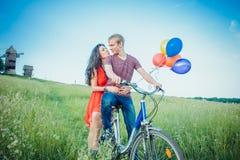 Jeunes couples heureux ayant l'amusement allant dehors pour un tour avec la bicyclette dans la campagne Photo libre de droits