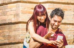 Jeunes couples heureux ayant l'amusement avec le smartphone à l'emplacement urbain de mur Image stock