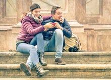 Jeunes couples heureux ayant l'amusement avec le smartphone dehors Photo stock