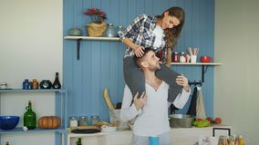 Jeunes couples heureux ayant l'amusement dans la cuisine à la maison La fille s'assied sur le cou du ` s d'ami Image stock