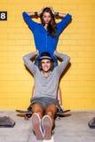 Jeunes couples heureux ayant l'amusement devant le mur de briques jaune Images libres de droits