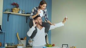 Jeunes couples heureux ayant l'amusement et parlant l'appel visuel en ligne dans la cuisine à la maison La fille s'assied sur le  Images libres de droits