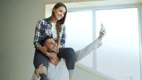 Jeunes couples heureux ayant l'amusement et parlant l'appel visuel en ligne dans la cuisine à la maison La fille s'assied sur le  Photos stock