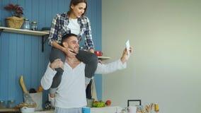 Jeunes couples heureux ayant l'amusement et parlant l'appel visuel en ligne dans la cuisine à la maison La fille s'assied sur le  Photos libres de droits