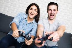 Jeunes couples heureux ayant l'amusement jouant le jeu vidéo à la maison Photographie stock libre de droits