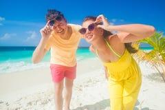 Jeunes couples heureux ayant l'amusement par la plage Photo libre de droits