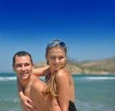 Jeunes couples heureux ayant l'amusement sur la plage. Photo libre de droits