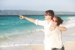 Jeunes couples heureux ayant l'amusement sur la plage tropicale. Image stock