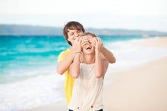 Jeunes couples heureux ayant l'amusement sur la plage tropicale. Image libre de droits