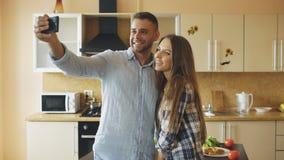 Jeunes couples heureux ayant la causerie visuelle en ligne dans la cuisine à la maison Photo stock
