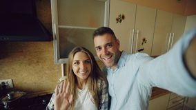 Jeunes couples heureux ayant la causerie visuelle en ligne dans la cuisine à la maison Photographie stock