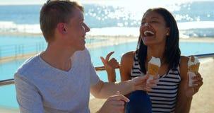 Jeunes couples heureux ayant la crème glacée sur la plage 4k banque de vidéos