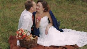 Jeunes couples heureux ayant le pique-nique dans le parc d'automne clips vidéos